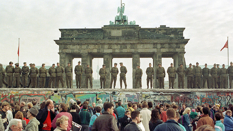 File photo of East Berlin border guards standing atop the Berlin Wall in front of the Brandeburg Gate on November 11, 1989. (Photo: Reuters)