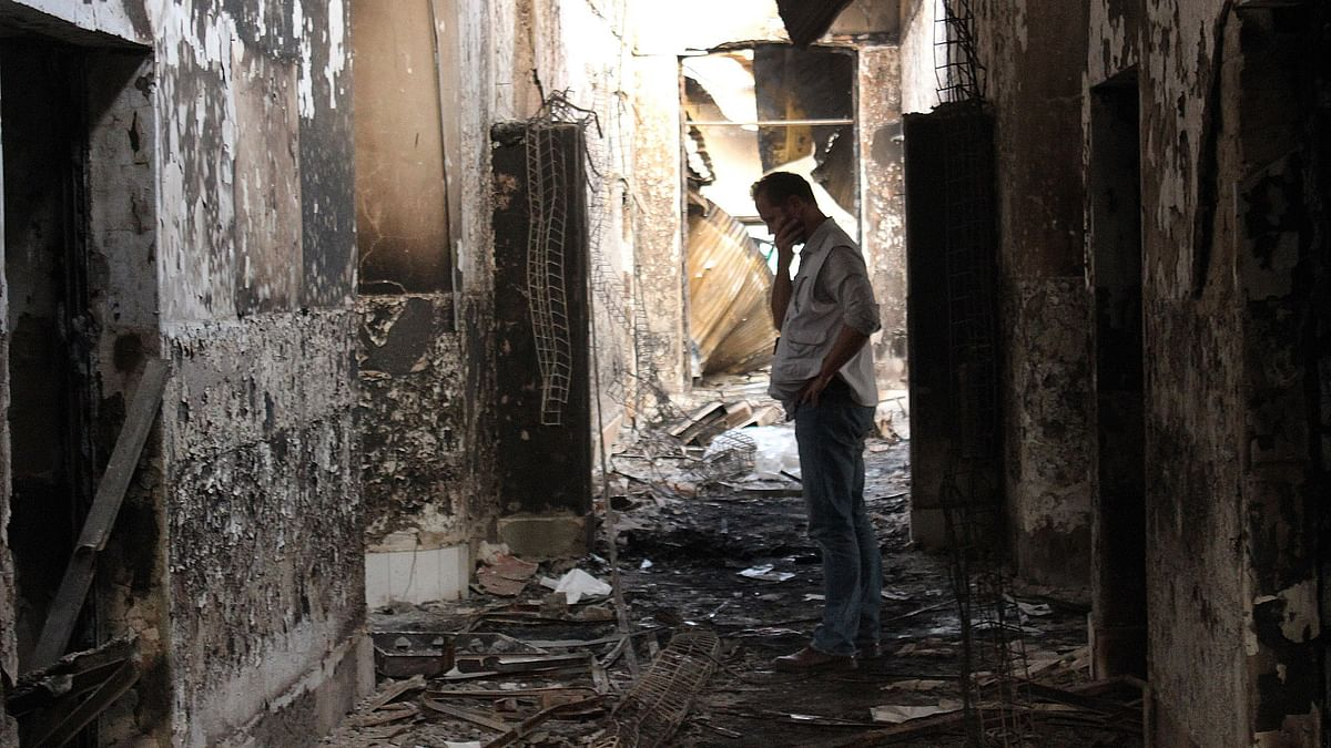 In this Friday, Oct. 16, 2015, file photo, an employee of Doctors Without Borders walks inside the charred remains of their hospital after it was hit by a U.S. airstrike in Kunduz, Afghanistan. (Photo: AP)