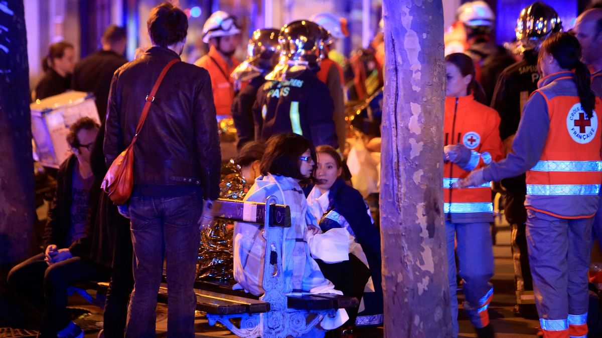 People rest on a bench after being evacuated from the Bataclan theatre in Paris following a shooting. (Photo: AP)