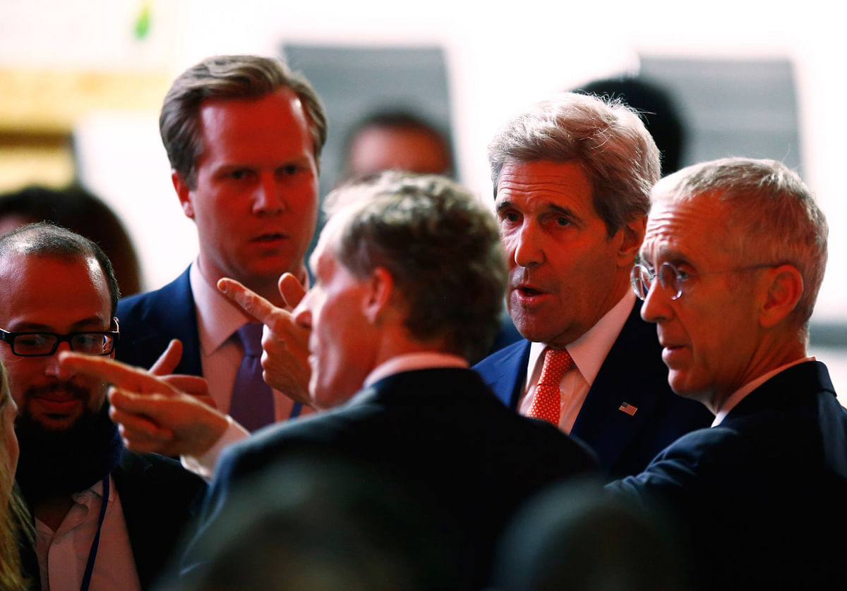 US Secretary of State John Kerry, second right, talks with unidentified people at the final conference at the COP21 (Photo: AP)