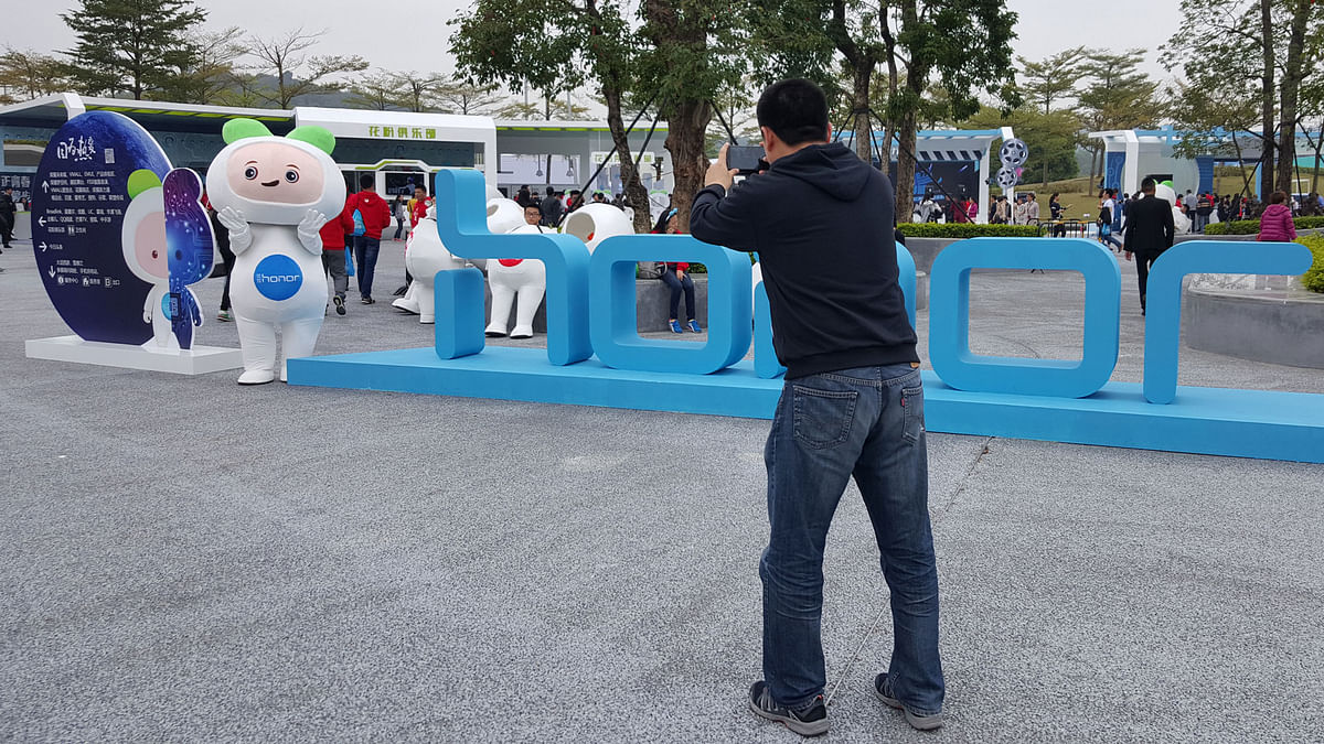 A man clicks the mascot of the Huawei Honor brand in Shenzhen. (Photo: <b>The Quint</b>)