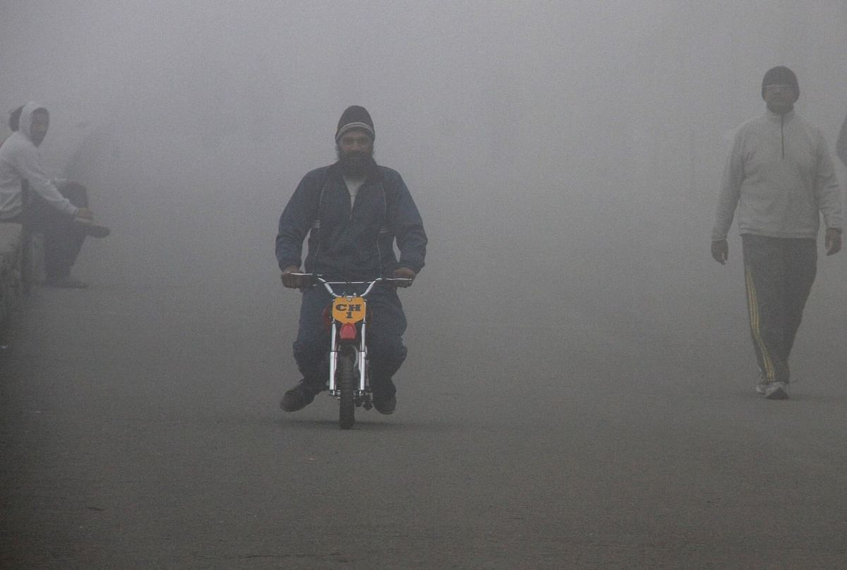 Man riding a motorcycle on a foggy morning in Chandigarh. (Photo: Reuters)