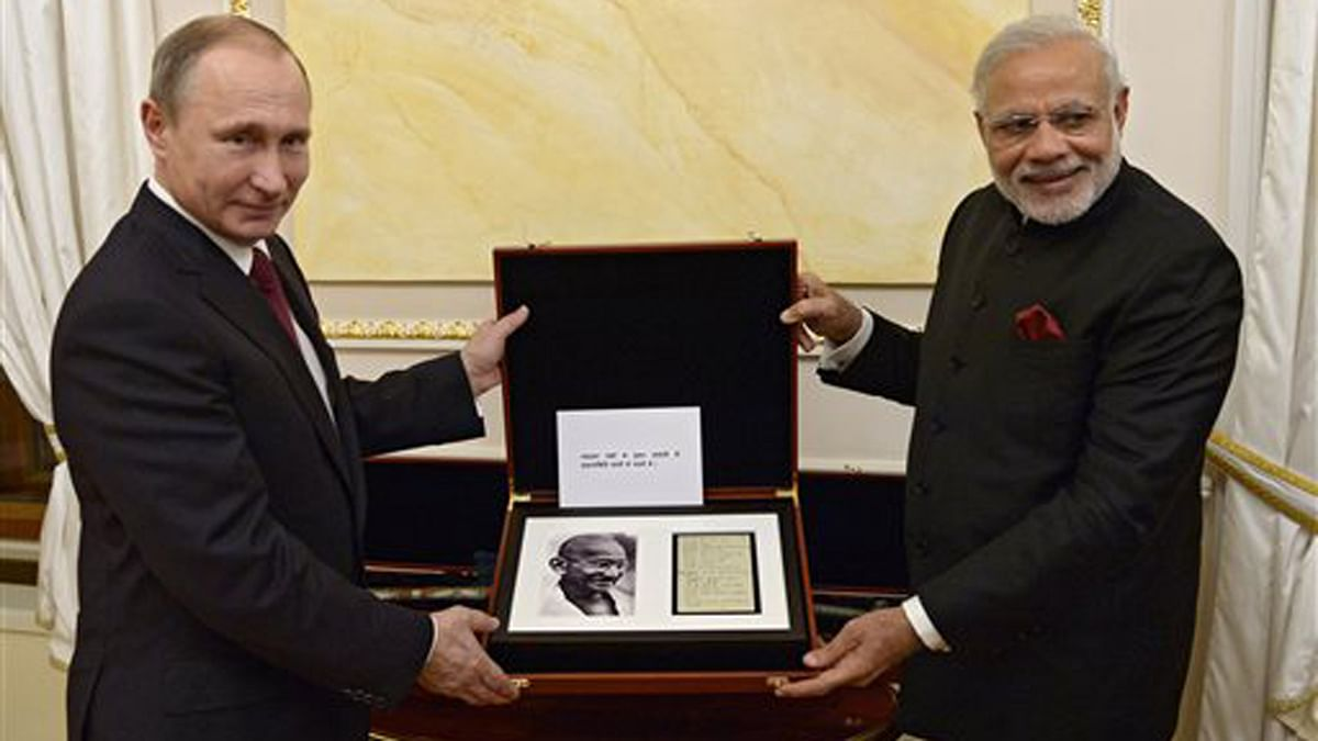Russian President Vladimir Putin presents Indian Prime Minister Narendra Modi a page from the diary of Mahatma Gandhi on Thursday. (Photo: AP)