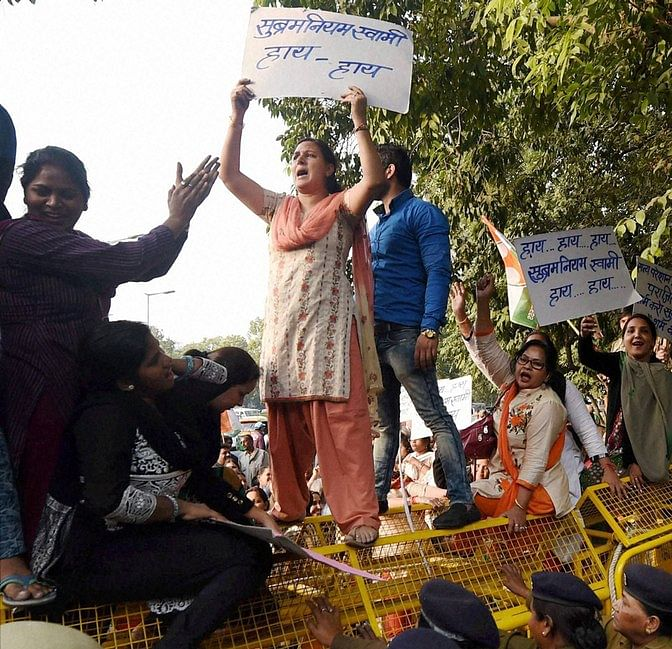 Congress women workers mount police barricades while protesting against the central government in the wake of the controversy generated by the <i>National Herald</i> case at Teen Murti in New Delhi on Tuesday. (Photo: PTI)