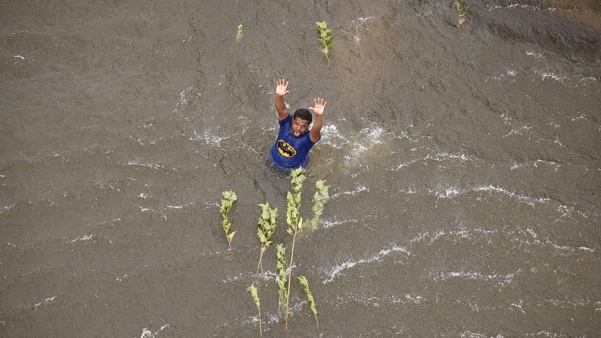 A man stranded in the floodwaters gestures to a coast guard helicopter for relief materials in Chennai, December 6, 2015. (Photo: Reuters)