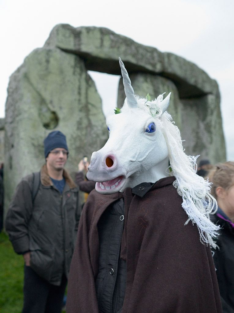 A person wearing a unicorn head joins others as people gather to celebrate the Winter Solstice at Stonehenge in England (Photo: AP)