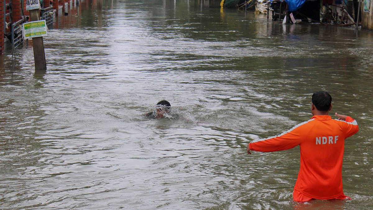 An NDRF official (right) arrives to rescue a boy who fell while wading through flood waters in Chennai. (Photo: <b>The Quint</b>)