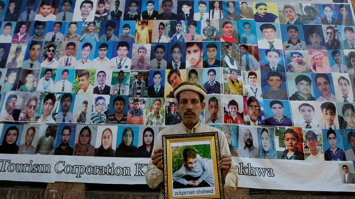 A Pakistani father holds a picture of his son who was killed in an attack, in front of photographs of other victims, ahead of the first anniversary of the Peshawar school attack on 15 December. (Photo: AP)