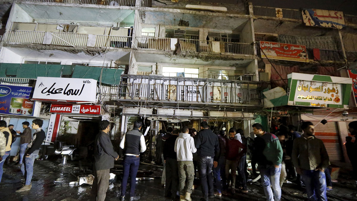 People gather at the site of a car bomb in New Baghdad on 11 January 2016. (Photo: Reuters)