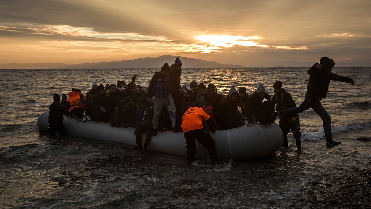 Refugees and migrants disembark on a beach after crossing a part of the Aegean sea from the Turkey's coast to the northeastern Greek island (Photo: AP)