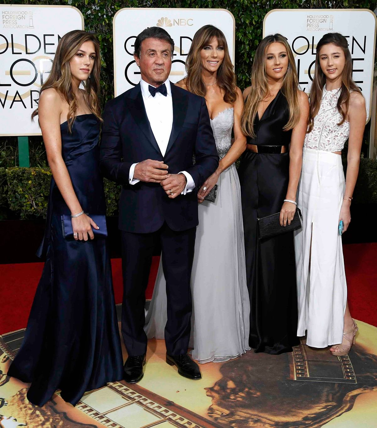 Sylvester Stallone poses with his wife and daughter in a deep blue suit (Photo: Reuters)