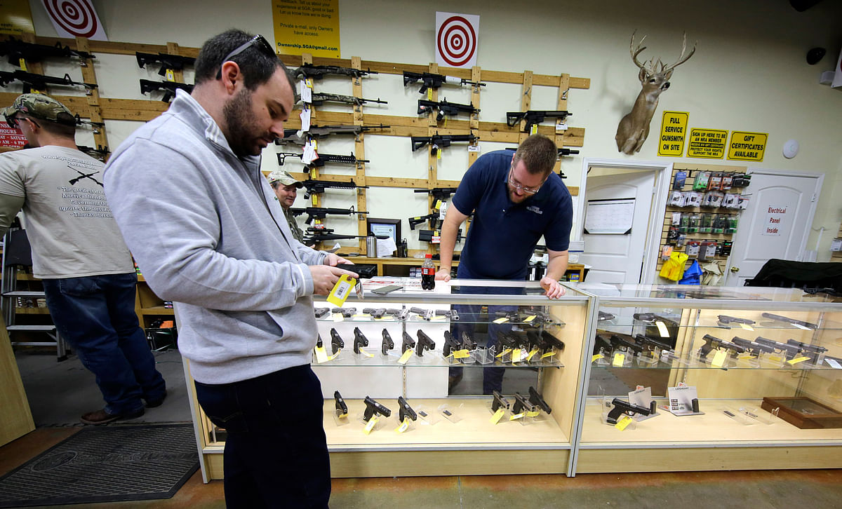 David Foley, center, looks as a handgun while shopping at the Spring Guns and Ammo store Monday, 4 January 2016, in Spring, Texas. (Photo: AP)