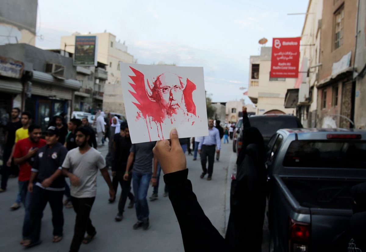 A Bahraini anti-government protester holds up a picture of Saudi Shiite cleric Sheikh Nimr al-Nimr, whose execution in Saudi Arabia was announced Saturday in Daih, Bahrain. (Photo: AP)