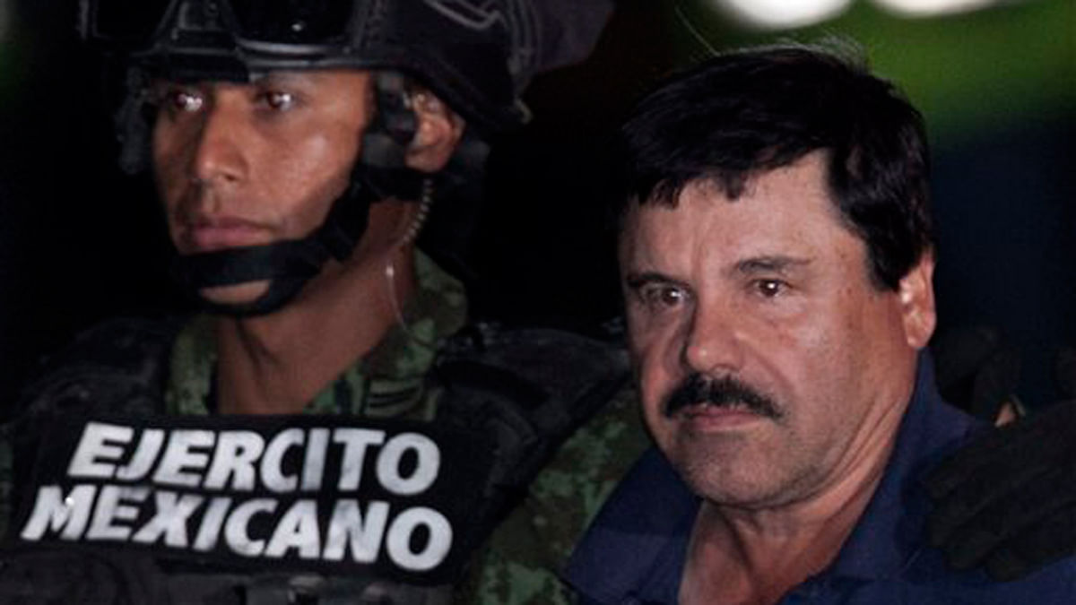 "Mexican drug lord Joaquin ""El Chapo"" Guzman, right, is escorted by soldiers and marines to a waiting helicopter. (Photo: AP)"