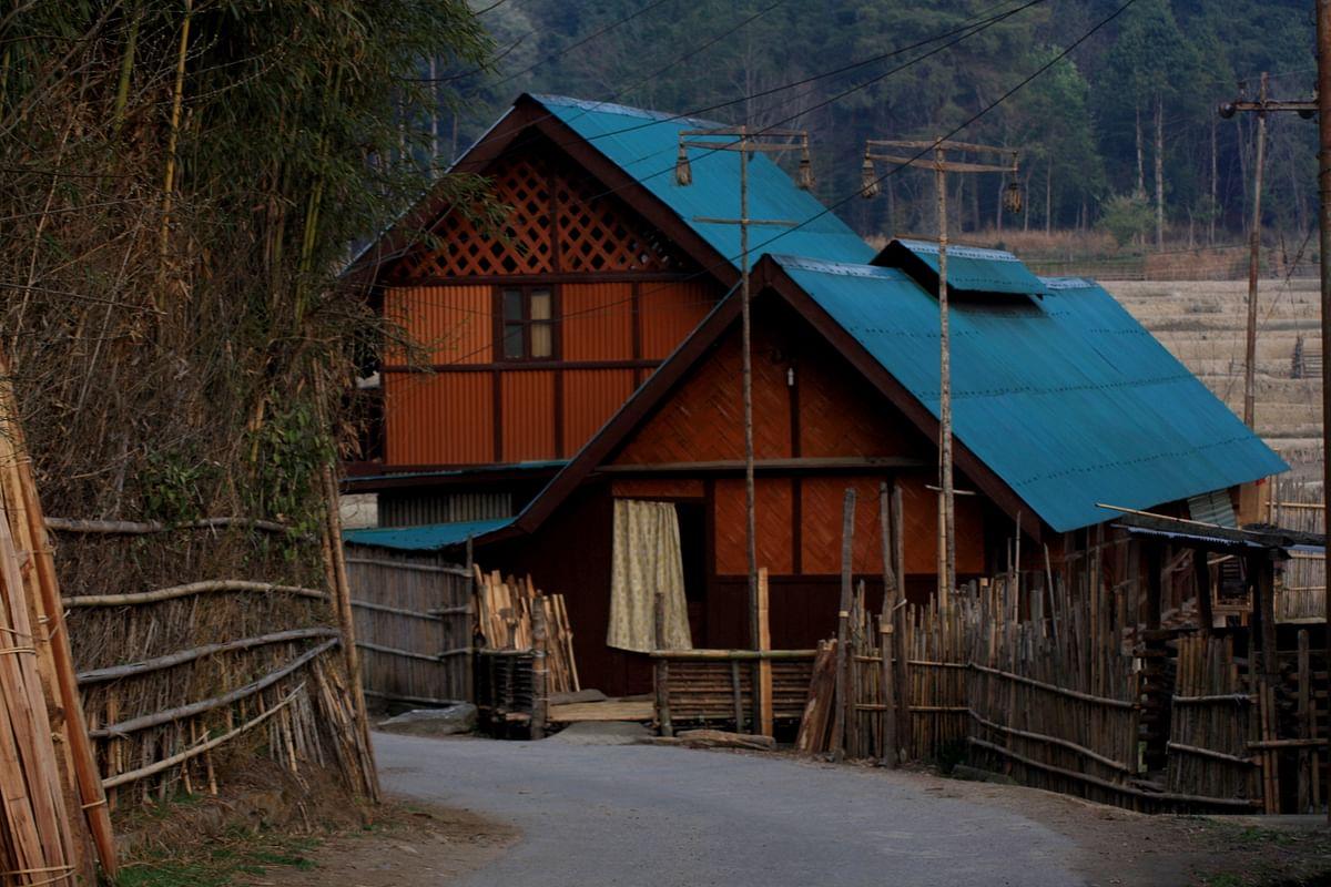 A home with its 'babo' – tall bamboo poles. (Photo Courtesy: Kushal Chowdhury)
