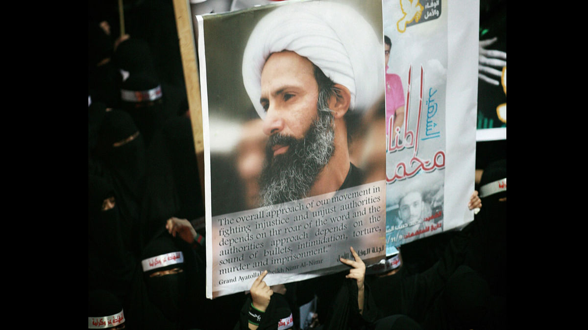 A Saudi anti-government protester carries a poster with the image of executed Shiite cleric Sheikh Nimr al-Nimr. (Photo: AP)