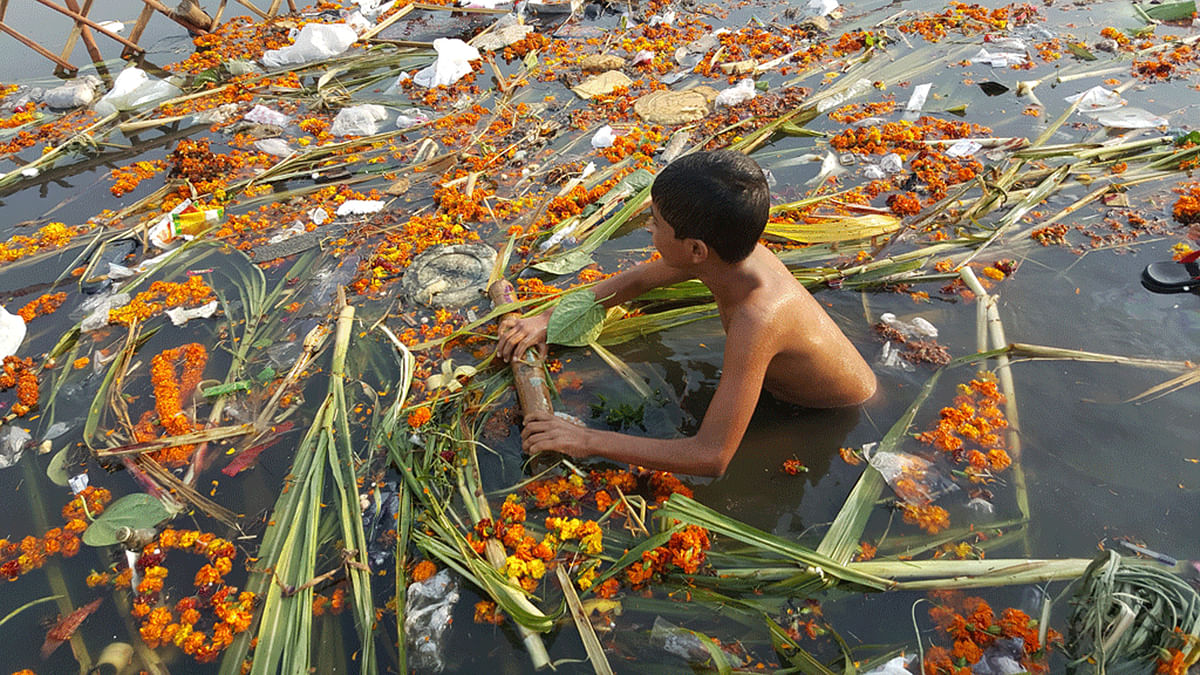 A boy wades through a canal near Kalyanpuri with the remains of the recently held Chhath Puja. (Photo: <b>The Quint</b>)
