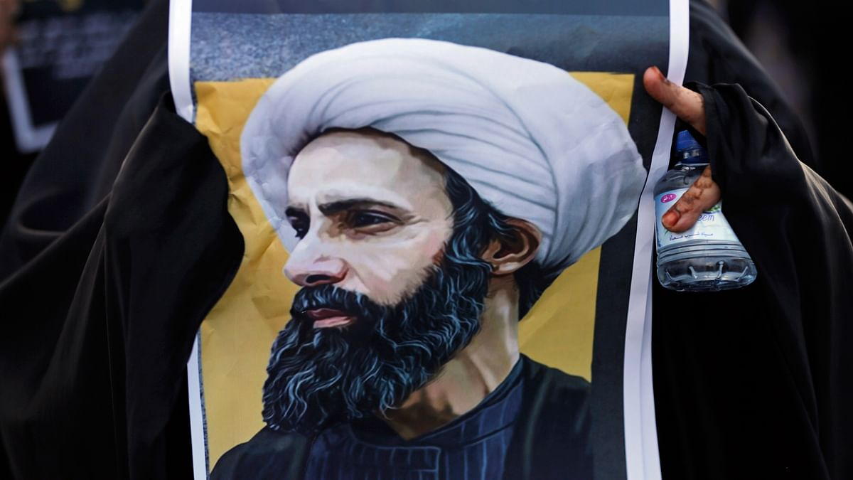 A Bahraini protester holds a picture of Saudi Shiite cleric Sheikh Nimr al-Nimr during a rally denouncing the execution of Shiite cleric Sheikh Nimr al-Nimr by Saudi Arabia, Sunday, 3 January 2016, in Daih, Bahrain. (Photo: AP)