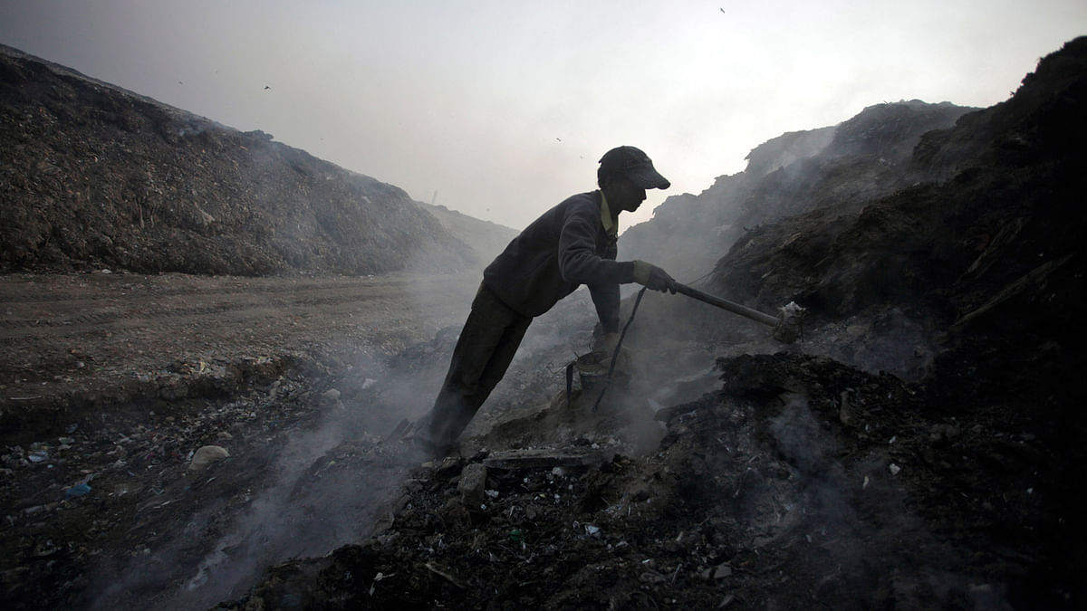 A scavenger sifts through ashes of waste for scrap metal in a garbage dump on the outskirts of New Delhi. (File photo: Reuters)