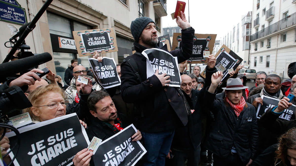 In this Thursday, 8 January 2015 file photo, journalists hold up their press cards during a minute of silence outside the Charlie Hebdo newspaper in Paris, a day after masked gunmen stormed the office. (File Photo: AP)