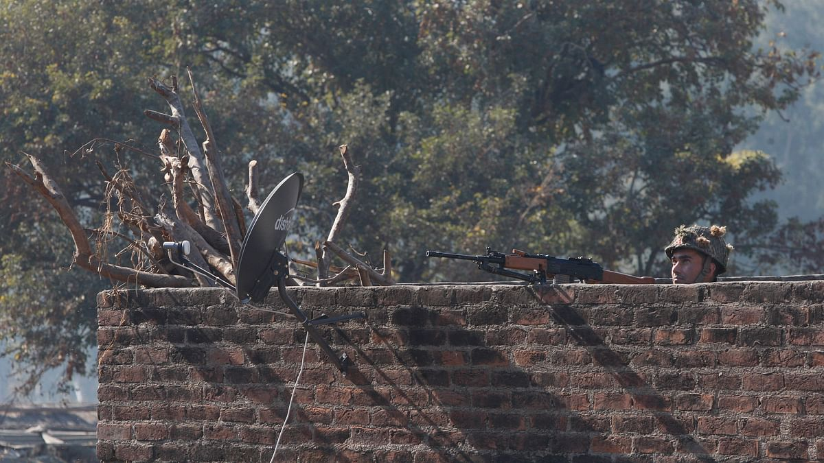 A soldier stands guard on a rooftop of a building outside the Pathankot airbase on Saturday, 2 January 2016. (Photo: AP)