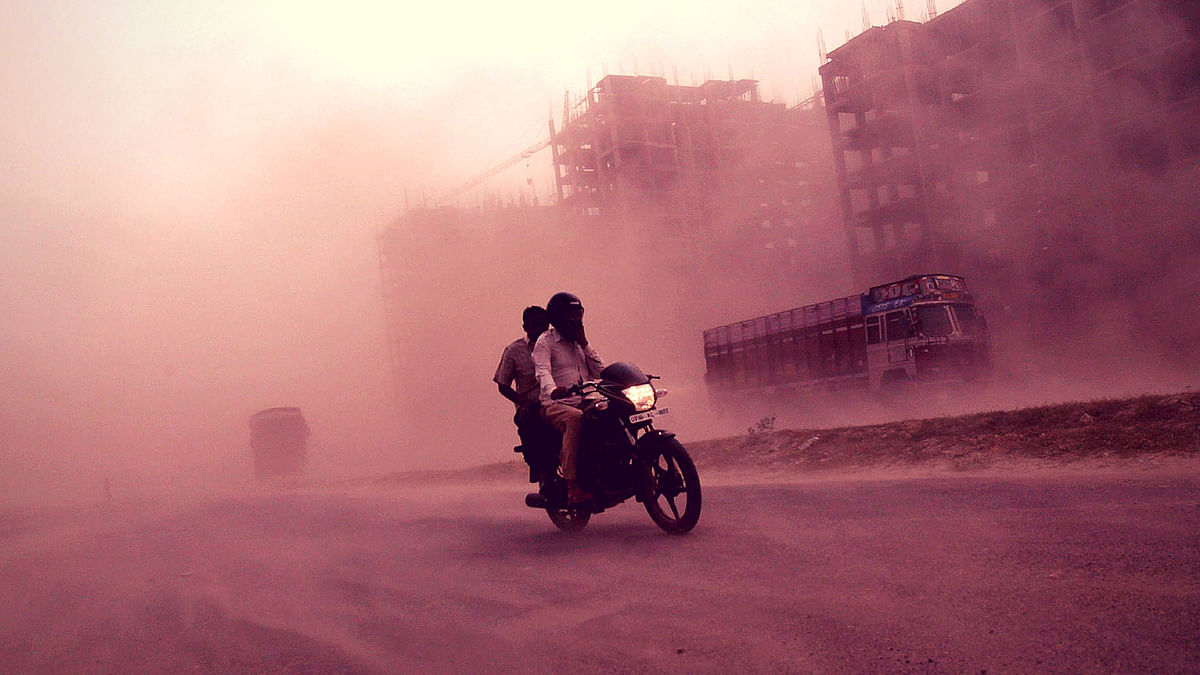 Men ride a motorcycle through a heavy dust storm along a road in Greater Noida on the outskirts of New Delhi on 23 October 2012.