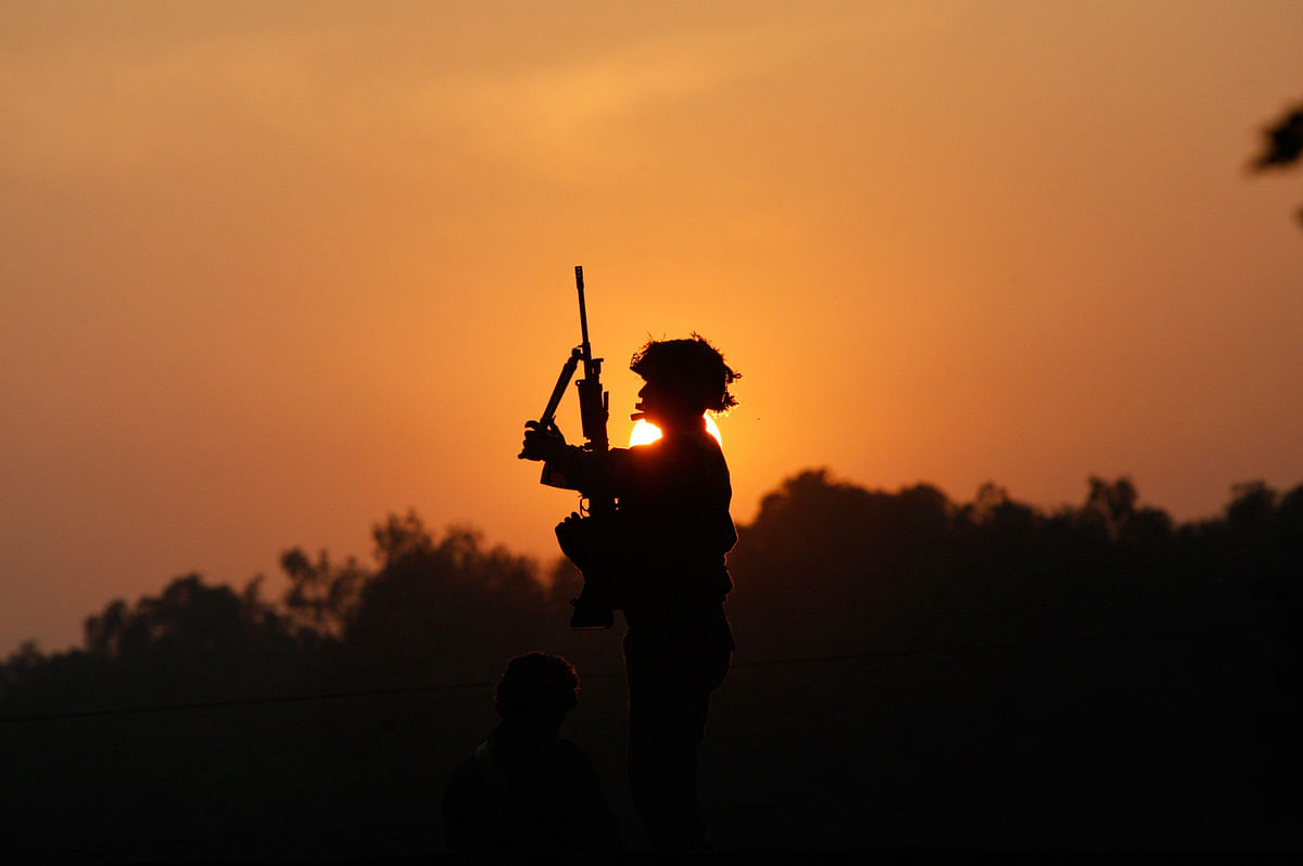 An Indian army soldier is silhouetted against the setting sun as he stands guard next to his colleague, sitting on the roof top of a house outside the Indian air force base in Pathankot, India. (Photo: AP)