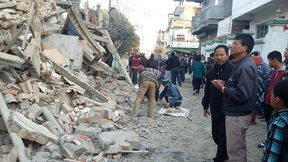 """People look at the rubble as the after effects of the quake in Manipur (Photo courtesy:<i> Manipur Times</i>' <a href=""""https://www.facebook.com/ManipurTimes/"""">Facebook Page</a>)"""