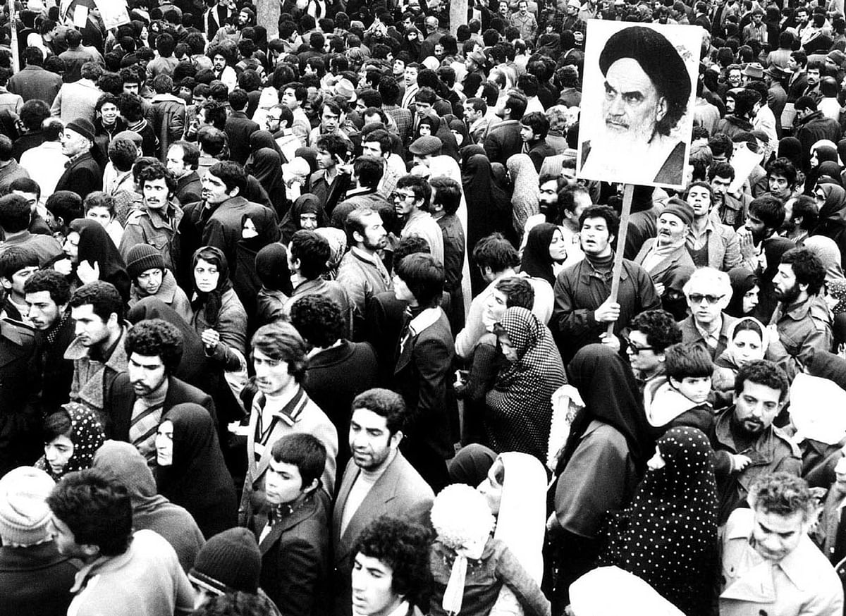 Supporters of the leader and founder of the Islamic revolution Ayatollah Khomeini hold his picture in Tehran during the country's revolution in February 1979. (File Photo: Reuters)