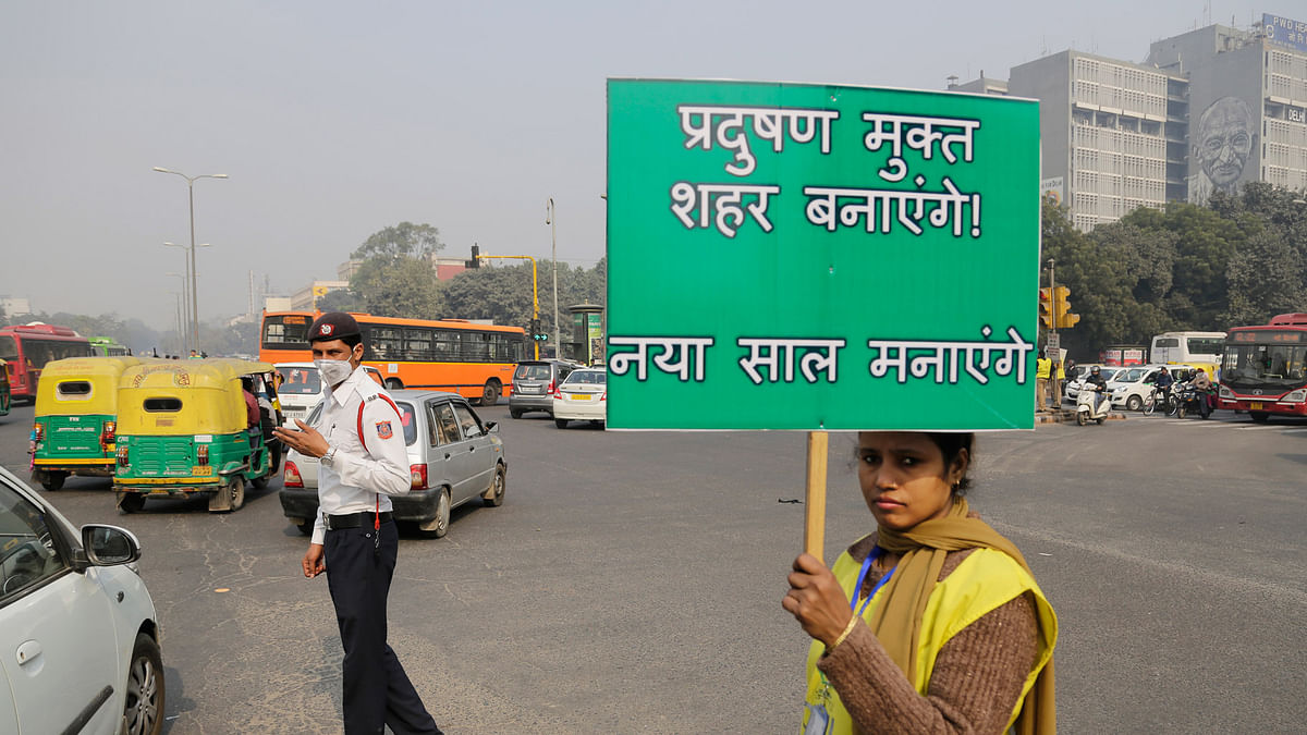"A volunteer holds a placard which reads ""We will make a pollution free city"" at a traffic intersection in New Delhi, Friday, January 1, 2016. (Photo: AP)"