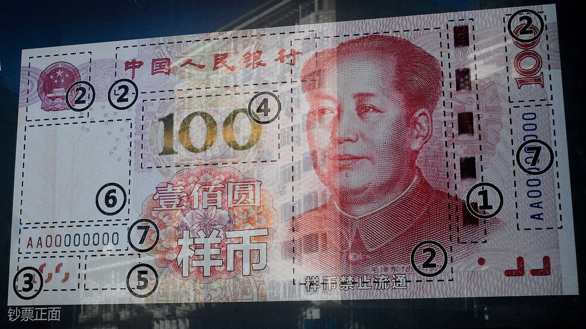 An office building is reflected on a new 100 Yuan note on display outside a bank in Beijing, Monday, January 11, 2016. (Photo: AP)