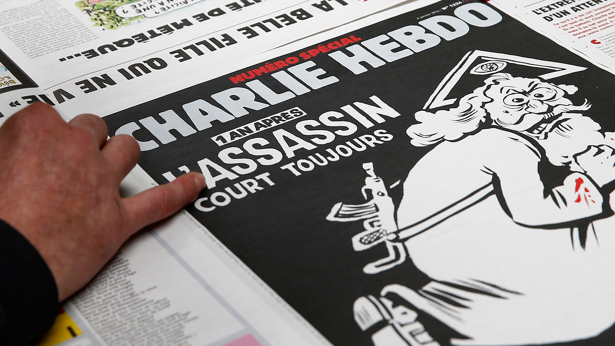 """An employee of a printing house checks a copy of the latest edition of French weekly newspaper Charlie Hebdo with the title """"One year on, The assassin still on the run"""". (Photo: Reuters)"""