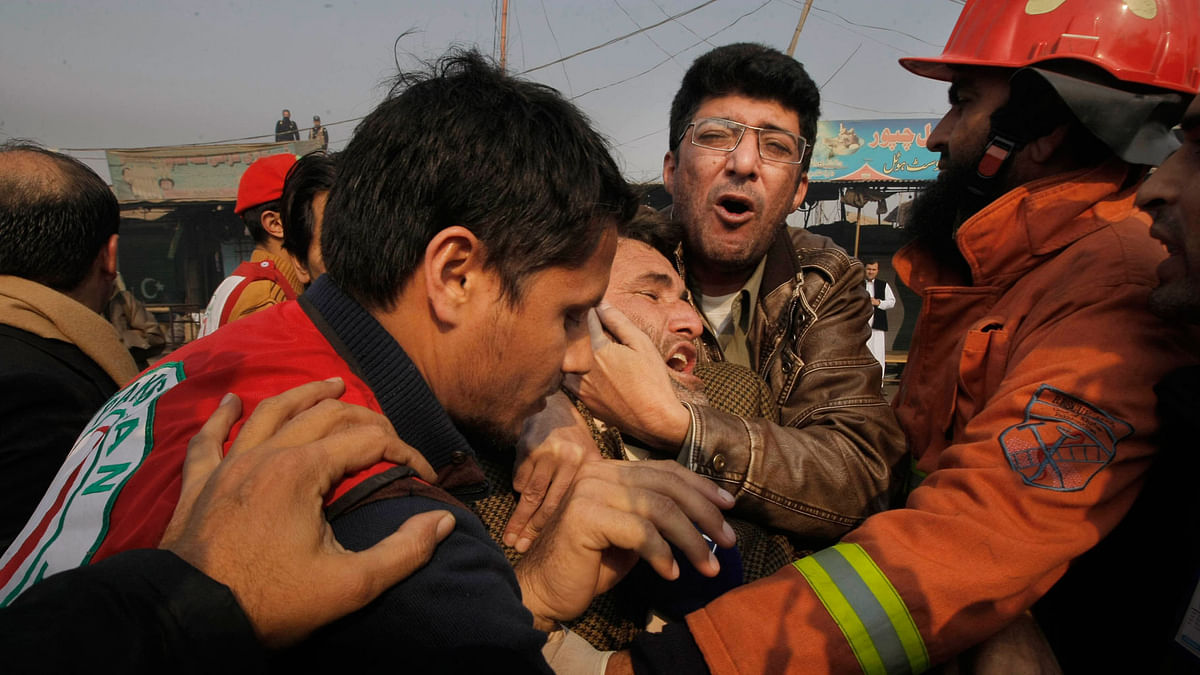 People comfort a man who lost a family member in the  suicide attack in Peshawar, Pakistan. (Photo: AP)