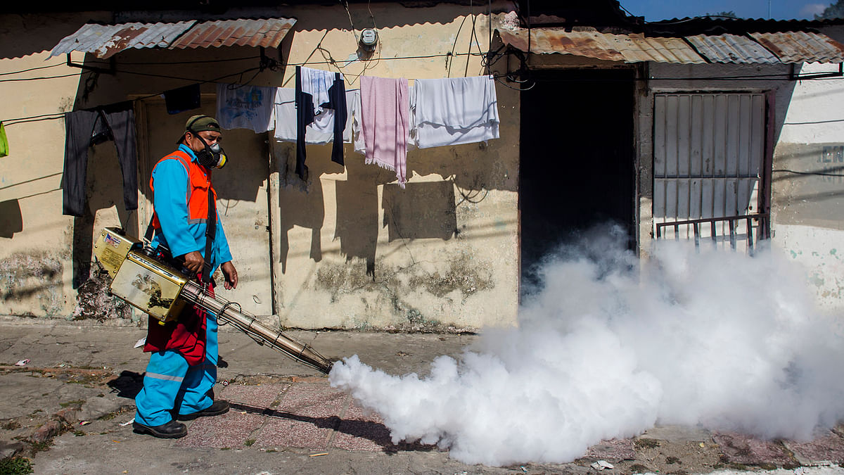 A city worker fumigates to combat the Aedes Aegypti mosquitoes that transmit the Zika virus, at the San Judas Community in San Salvador, El Salvador, on Tuesday, 26 January 2016.  (Photo: AP)