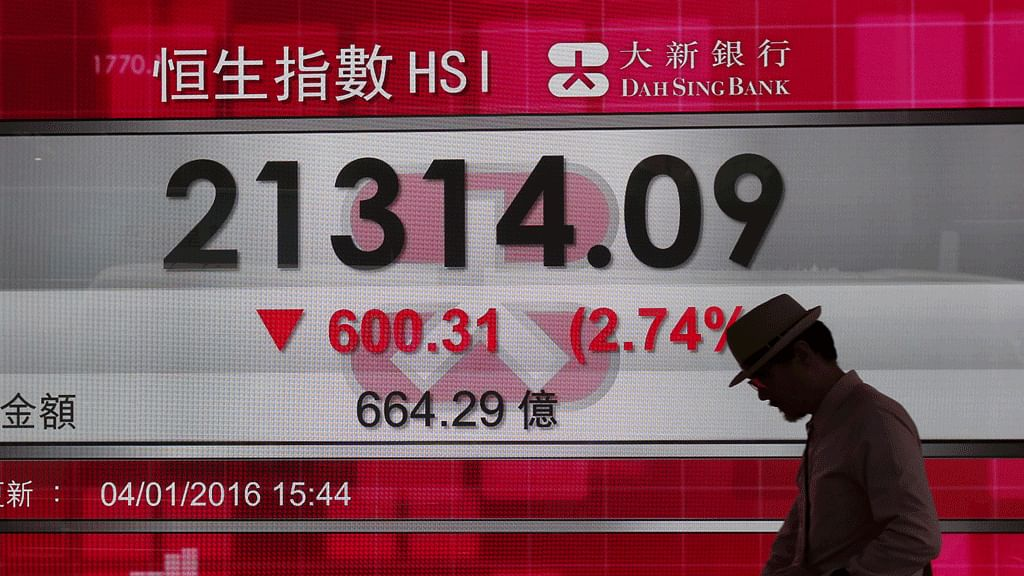 A man walks past a panel displaying the benchmark Hang Seng index during afternoon trading in Hong Kong on January 4, 2016. (Photo: Reuters)