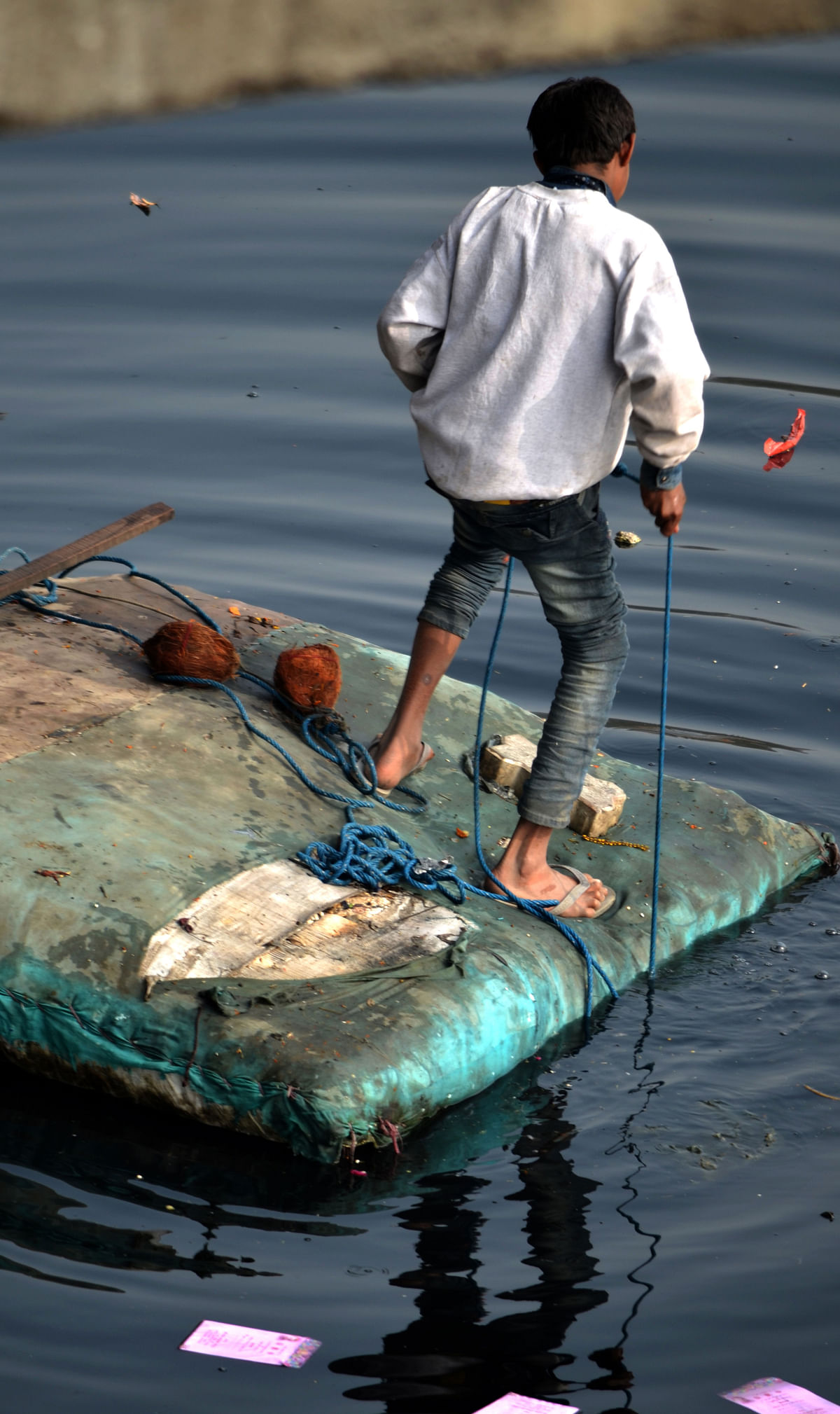 A child collecting garbage from the river. (Photo: <b>The Quint</b>)