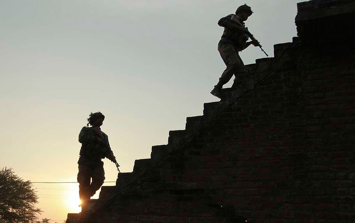 Indian army soldiers climb up the stairs of a residential building outside the Indian air force base in Pathankot. (Photo: AP)