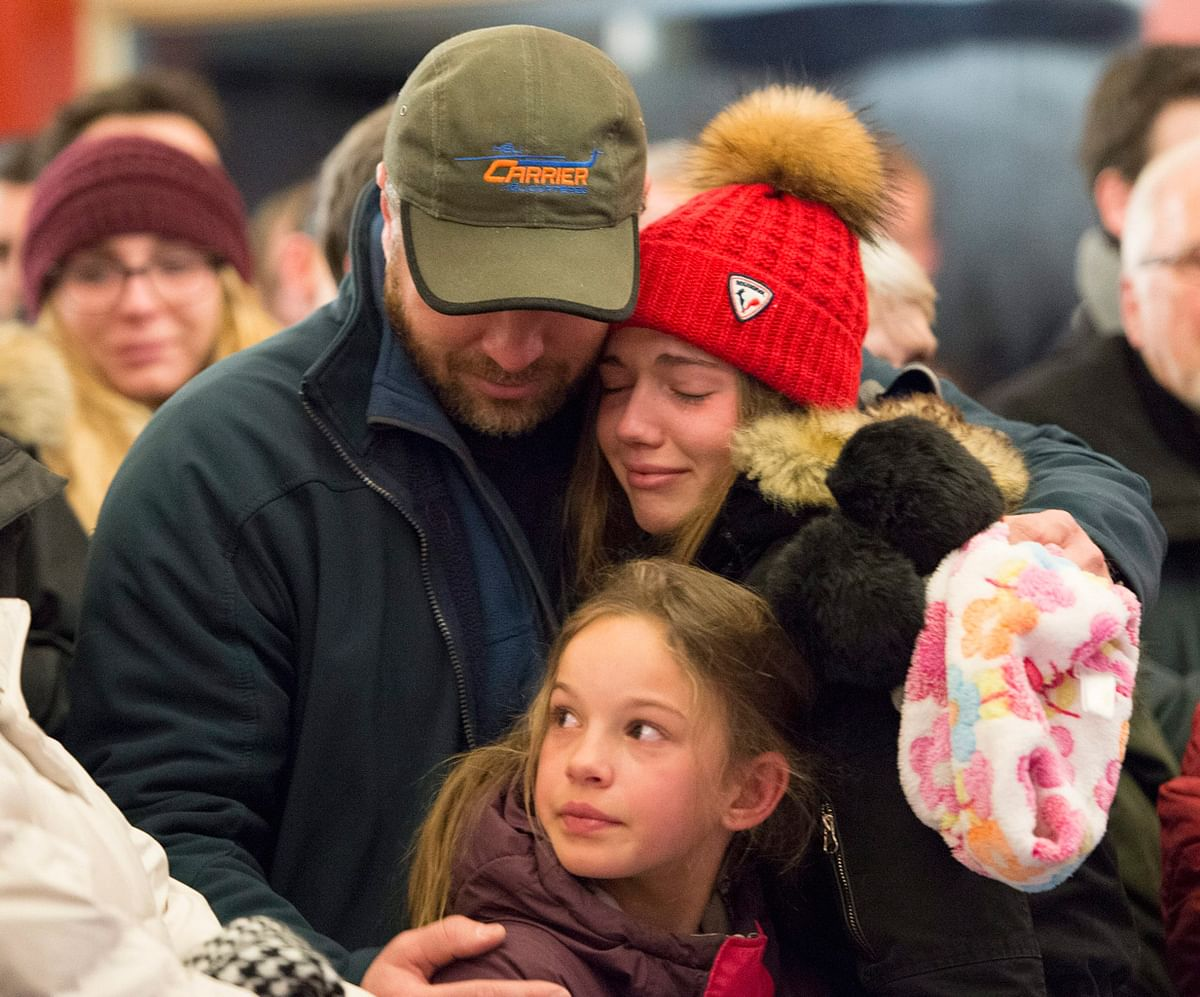 A man who lost his father in the attacks, grieves with his two daughters. (Photo: AP)