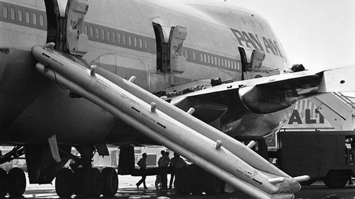 Pakistani policemen investigate the Pan Am jetliner under the emergency chute in Karachi, Pakistan on Saturday morning, 6 September 1986. (Photo: AP)