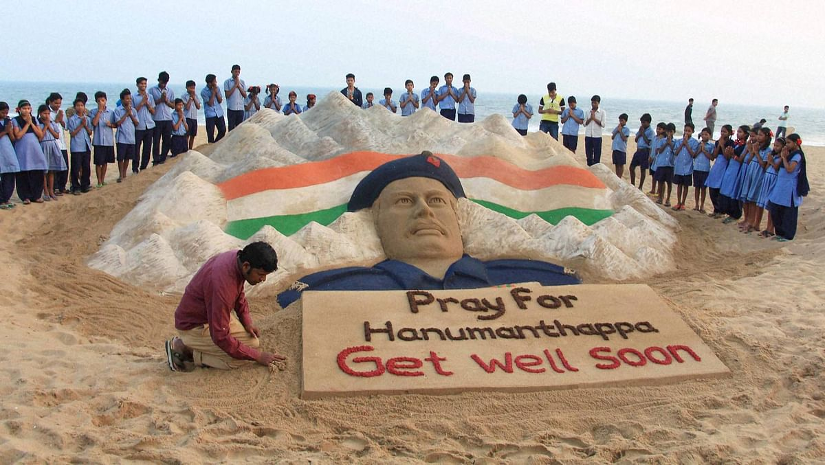 Renowned sand artist Sudarshan Patnaik prays for Hanumanthappa. (Photo: PTI)