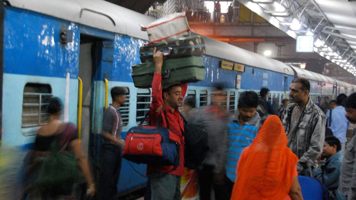 A porter carrying luggage at a Delhi railway station.
