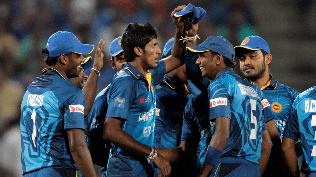 Kasun Rajitha celebrates a wicket with his teammates in the first T20 at Pune. (Photo: AP)