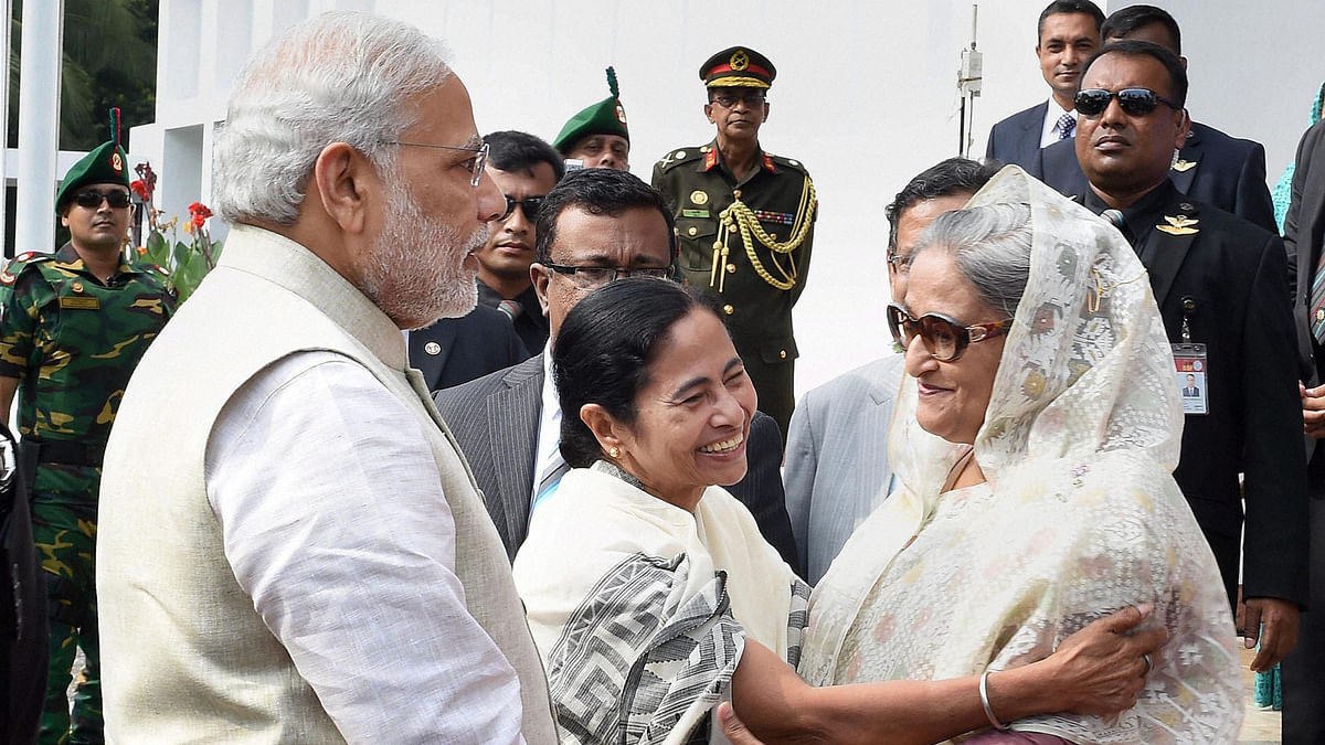 In this file photo, Prime Minister Narendra Modi looks on as Bangladesh Prime Minister Sheikh Hasina and West Bengal Chief Minister Mamata Banerjee hug each other at the flag off ceremony of bus services between Bangladesh and India. (Photo: PTI)