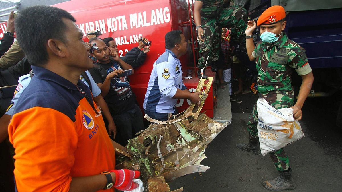 Rescuers carry a part of Indonesian Air Force plane which crashed into a house in Malang, East Java, Indonesia. (Photo: AP)