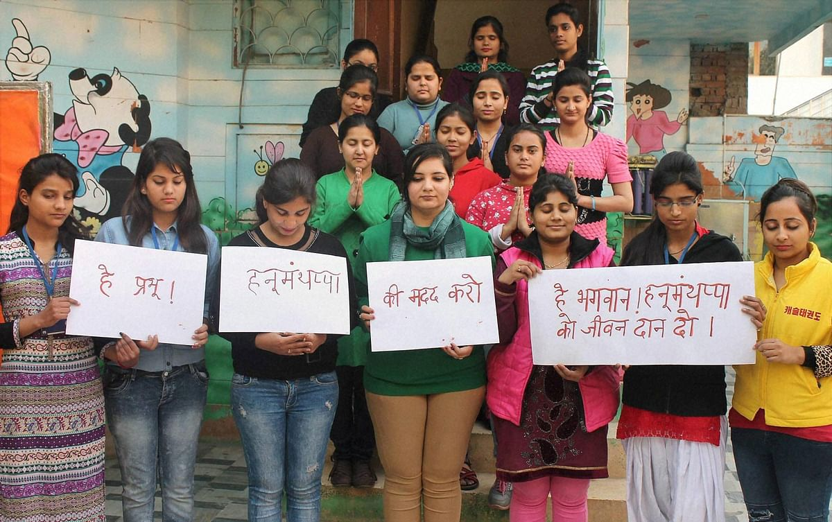 Students of Khazani Womens Vocational Institute pray for army man Hanumanthappa Koppad in Faridabad. (Photo: PTI)