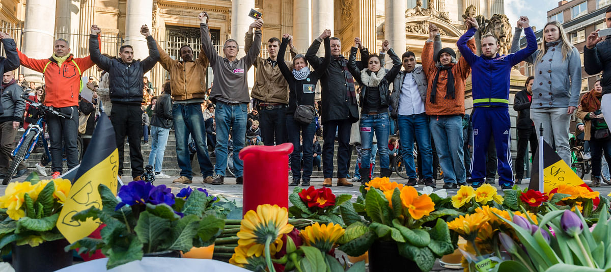People hold hands in solidarity near a memorial to attack victims outside the stock exchange in Brussels on Tuesday, March 22, 2016. (Photo: AP)