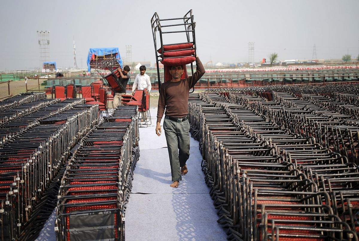 A worker carries chairs at the venue of the World Culture Festival on the banks of the Yamuna. (Photo: Reuters/Anindito Mukherjee)