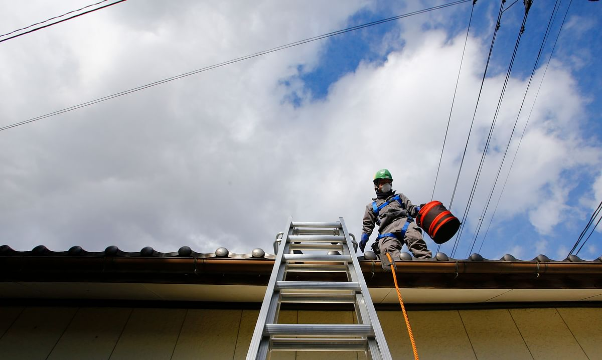 A worker wearing a mask stands as he cleans radiation-exposed roof tiles at a private house in Minamisoma, Fukushima Prefecture, northeastern Japan. (Photo: AP)