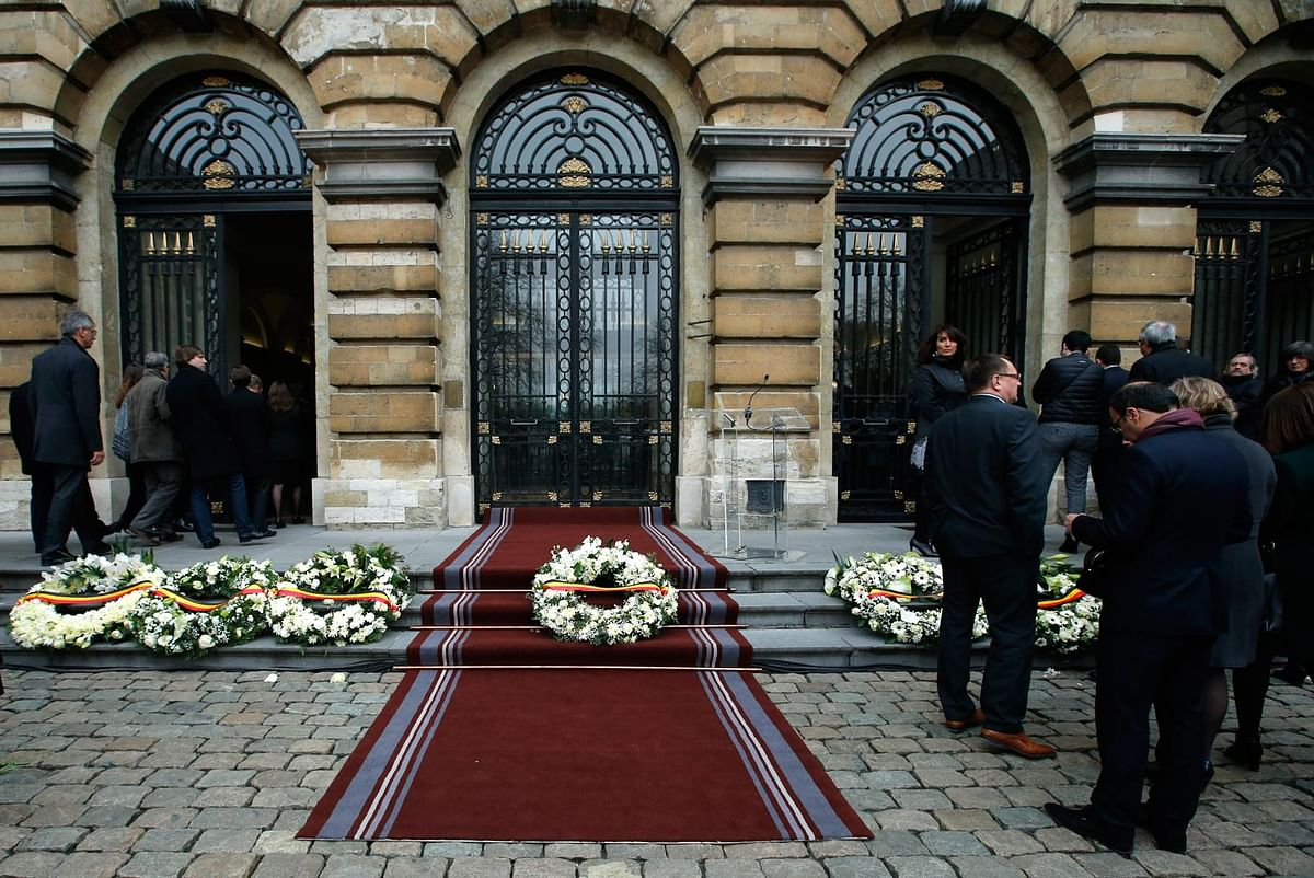 Belgian lawmakers walk past wreaths laid on the grounds of the Parliament building in Brussels (Photo: AP)
