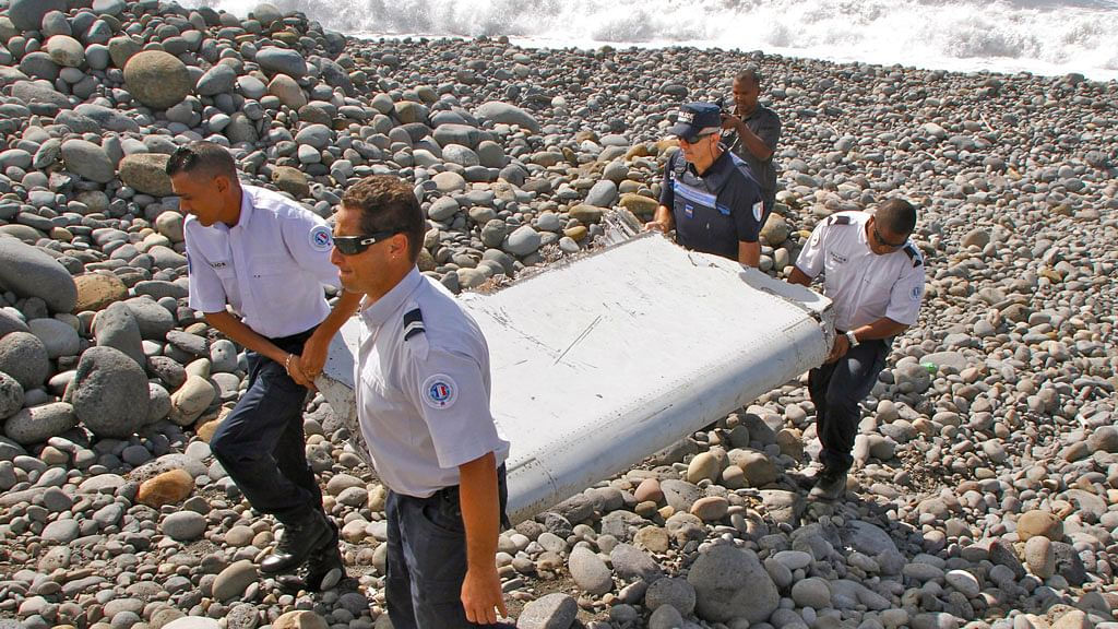 French police officers carry a piece of debris from a plane in Saint-Andre, Reunion Island, which was later confirmed to belong to MH370. (Photo: AP)